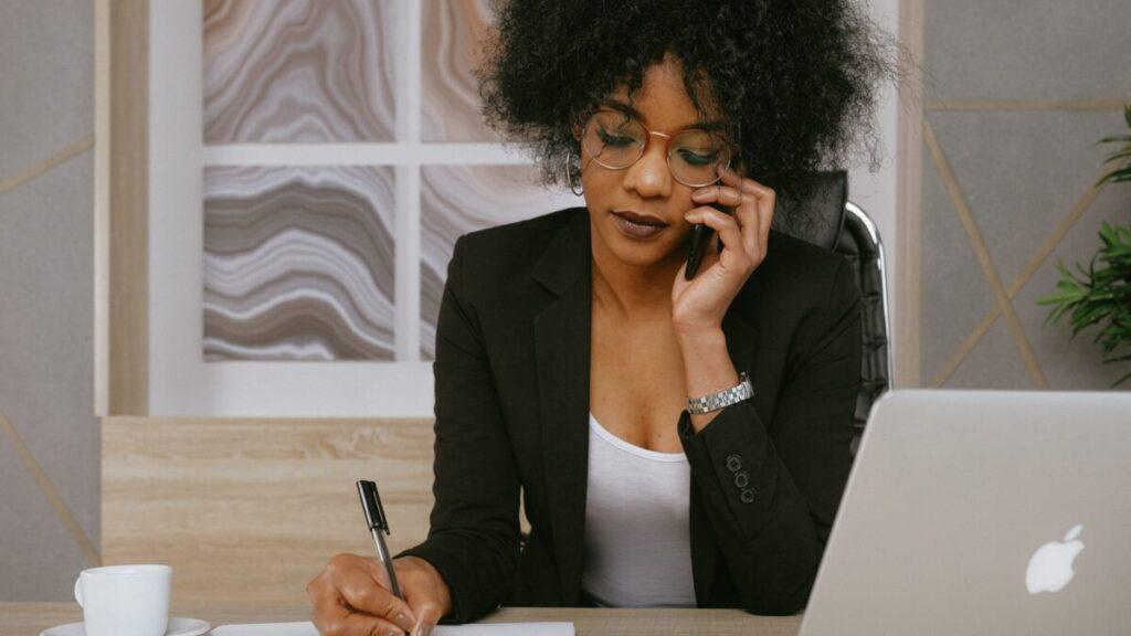 メモを取りながら電話をする女性