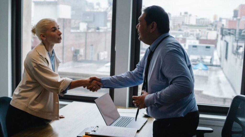 会議室で女性と男性が握手