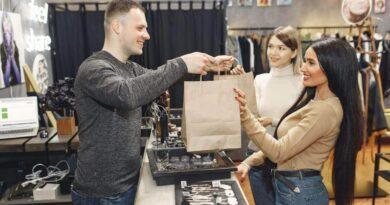 アパレルストアで精算後、買い物袋を受け取る女性