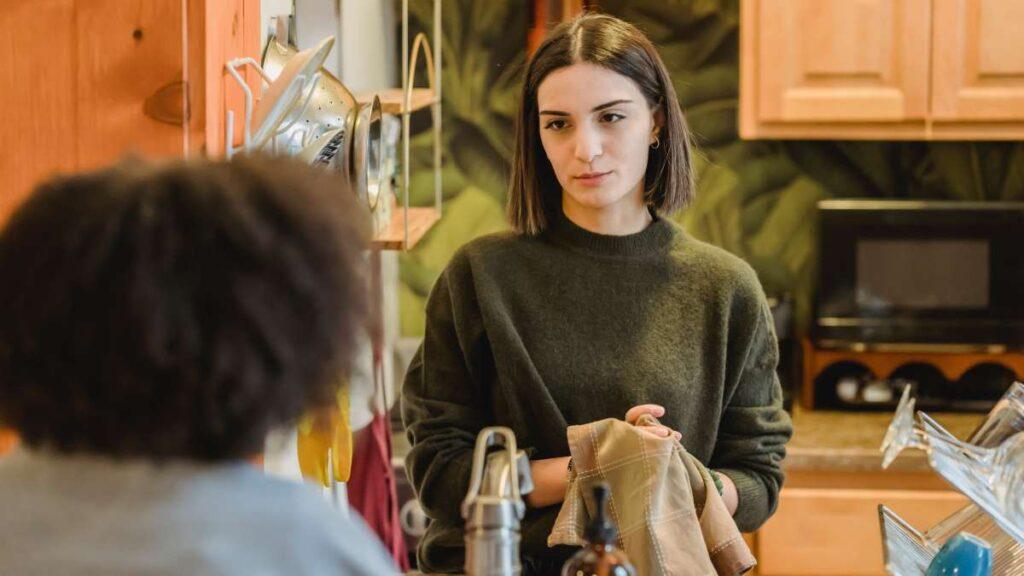 キッチンのカウンター越しに、キッチンに座っている人に何かを頼もうとしている女性