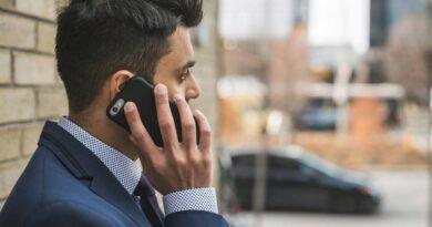 ビルの外で携帯で誰かと話すビジネスマン