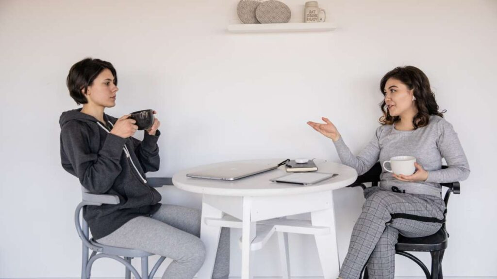 コーヒーを飲みながら話をする二人の女性