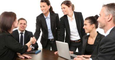 笑顔で握手をするビジネスウーマンとその同僚